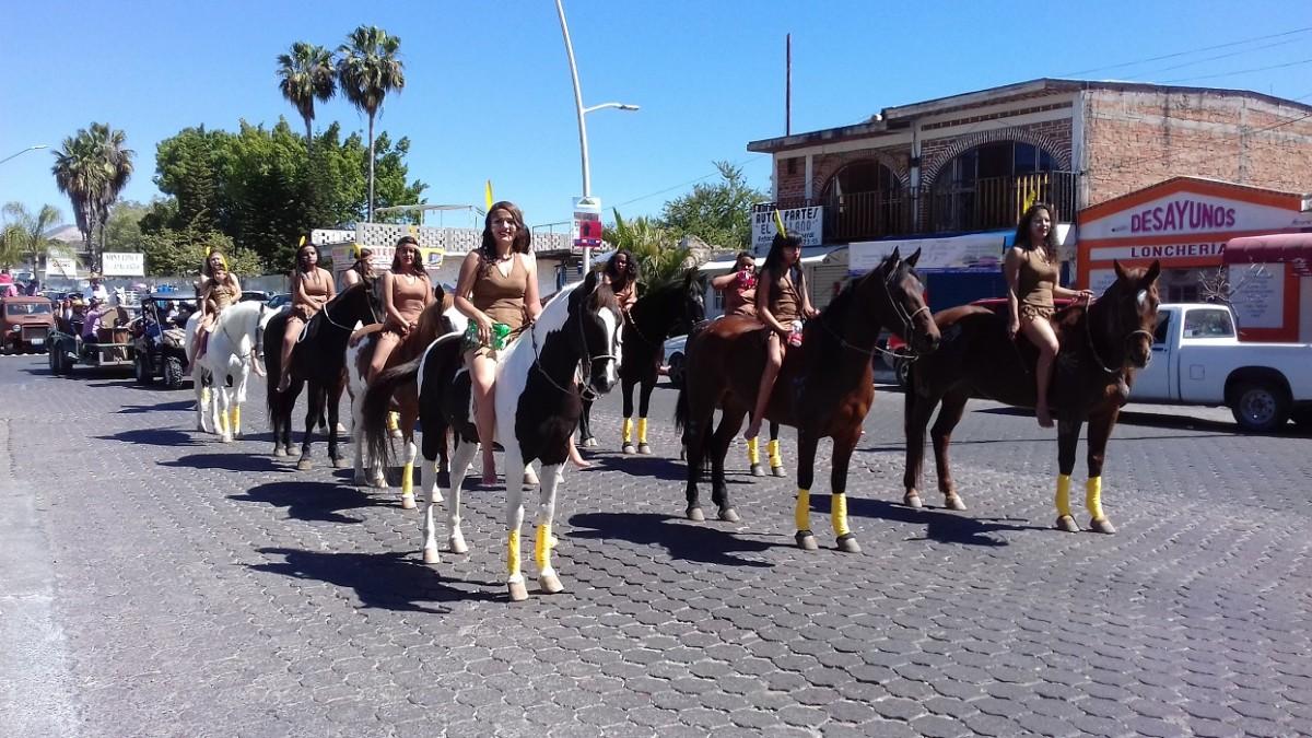 Un grupo mujeres vestidas de indias montadas en caballos.